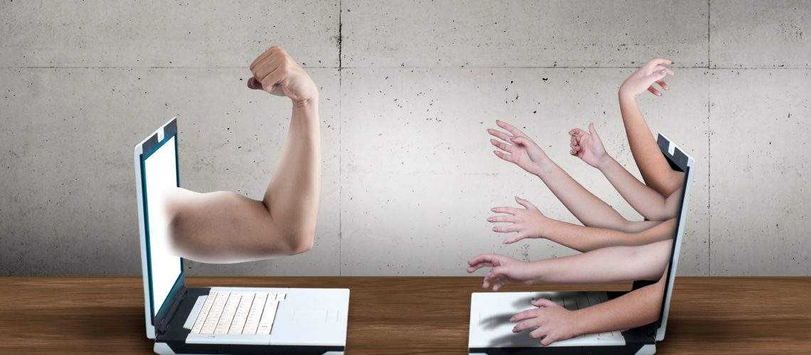 Two laptop with arms pointed to eachother. Cyber bully concept. Online conflict between people. Human rights argue.