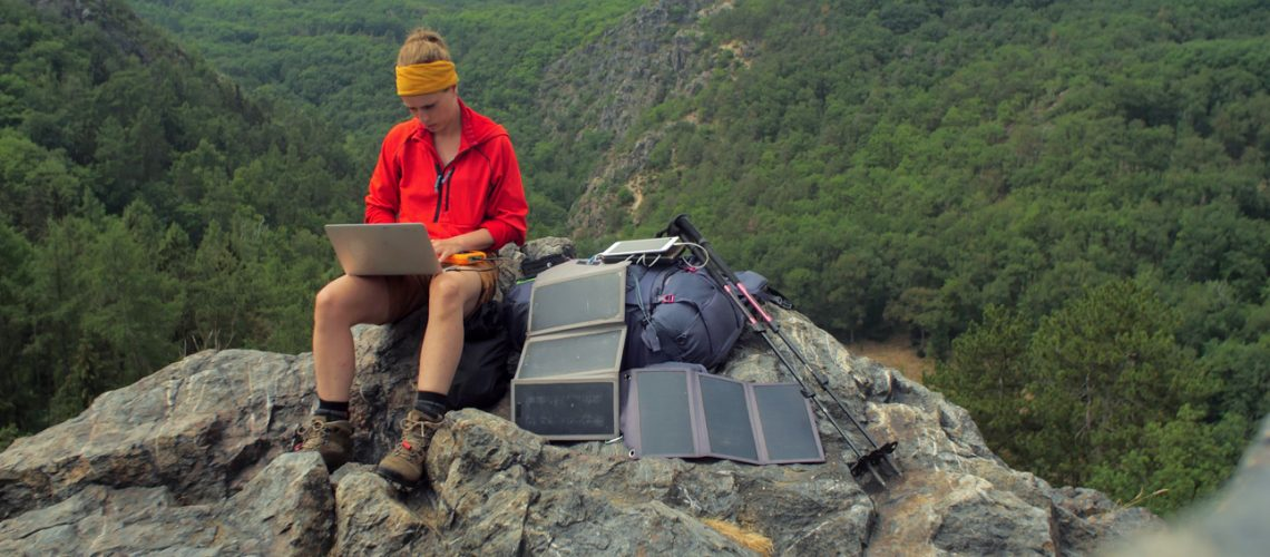 Caucasian,Female,Hiker,Sitting,On,A,Rock,While,Working,On