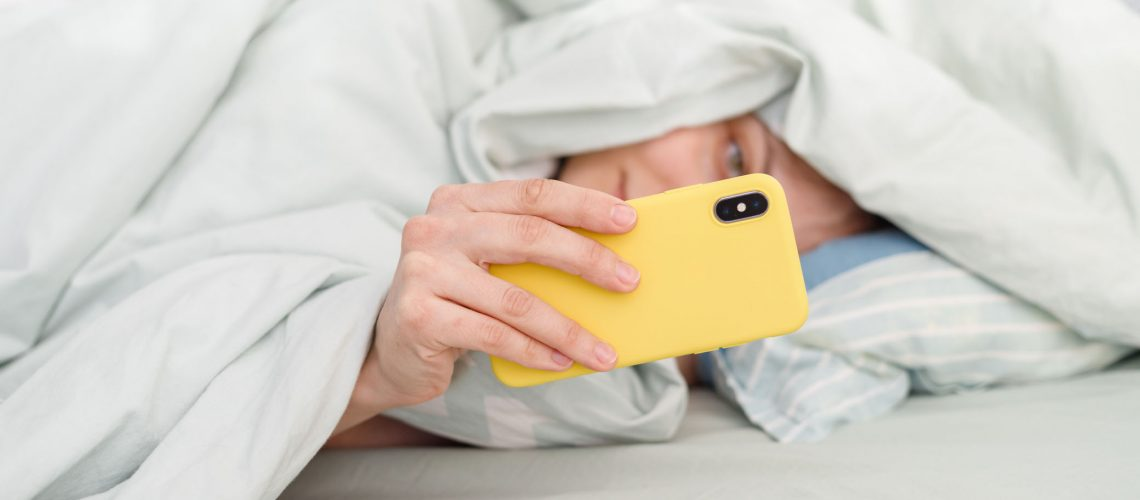 European,,Caucasian,Woman,In,Bed,With,Phone,,Holding,Smartphone,In